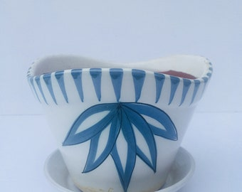 White planter with blue painted  flower design and dish.