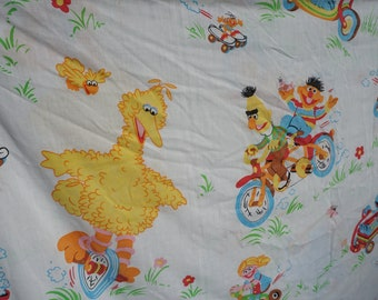 JC Penneys vintage Sesame Street twin flat sheet with Big Bird and friends on scooters, bikes, trikes, soap box car, skateboard