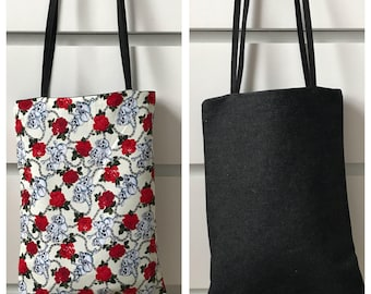 Small reversible shoulder bag in black denim & skulls cotton.