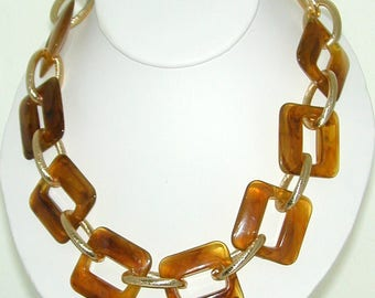 Bold amber-colored acrylic links on gold aluminum links