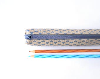 Small pencil case/zipper pouch in light brown with blue hearts in a grid of dots, with a light grey zip and a solid grey lining