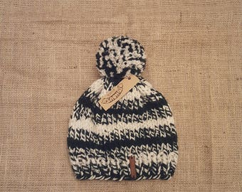Pighouse adult chunky knit handmade dark green and cream cosy winter bobble hat with extra large mixed pom pom.