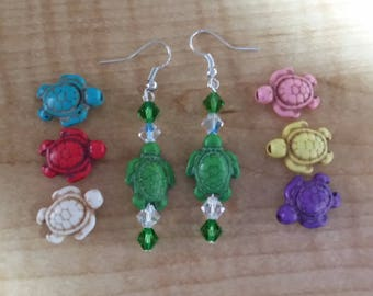 A painted Turtle is the focal point of these earrings. It is contrasted with Swarovski bicone beads