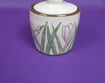 Lovely studio pottery lidded canister. Decorated with lilac crocus flowers and leaves.