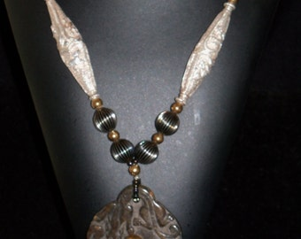 Necklace of carved stone, Bali silver, and golden glass with melon beads