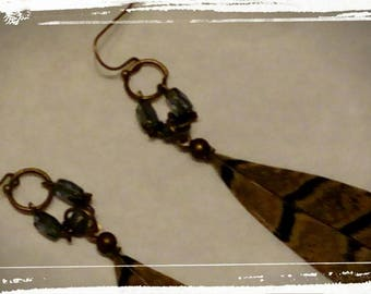 A pair of earrings with pheasant feather and glass beads