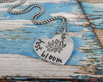 Aluminium medium heart with the words just bloom and the symbol of a lotus flower.