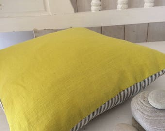 Yellow linen cushion with black ticking backing.