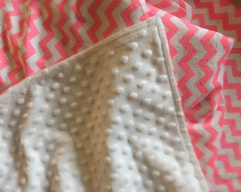 A blanket in a minky chevron print in neon pink and white . The back is a white minky dot.