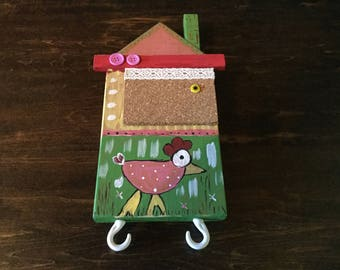 Decorative wooden house with Cork and hooks.