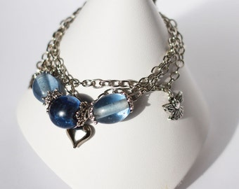 Multistrand silver charm bracelet with blue glass beads