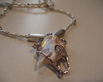 Aphrodite. Mother-of-pearl pendant in a beaded necklace.