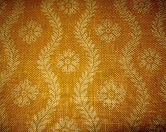 A vintage fabric or vintage burlap canvas printed with flowers (a little mustard color)