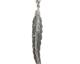 long pendant necklace with black rhinestoned leaf