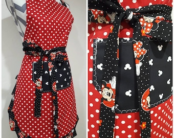 Adult apron. Woman's apron. Red with white polka dots on main. Black pocket with Minnie mouse print on ties and frills.