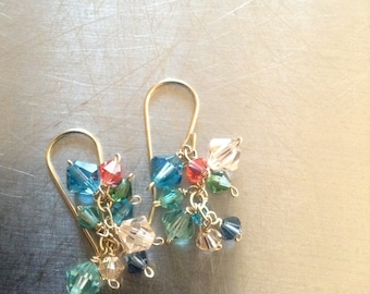 Swarovski Crystal clusters in Teal green, teal blue, peach and coral dangle from gold fill ear wires. 3cm/