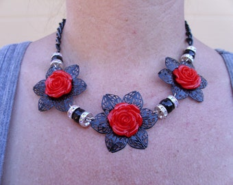 Black flower filagree with red rose cabachon and black beads with rondelles, matching earrings