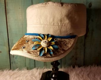 Canvas colored cargo cap with brown and white cowhide and blue and yellow flower accent
