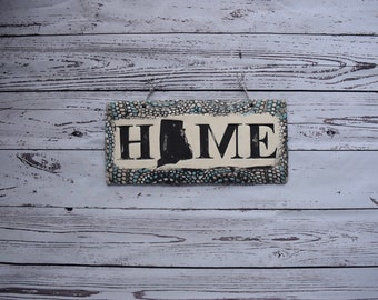 State silhouette HOME sign in charcoal gray with pale blue, white and ivory highlights.  Your choice of state in place of the O!