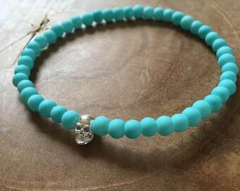 Blue Silver Skull: an elastic beaded bracelet with silver skull and matte lightblue glass beads.