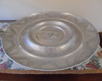 """Hand Wrought aluminum lazy Susan by Wilson. Floral carved revolving multi tiered scalloped edge plate & scalloped pedestal.14-1/2D,3-1/4""""H."""