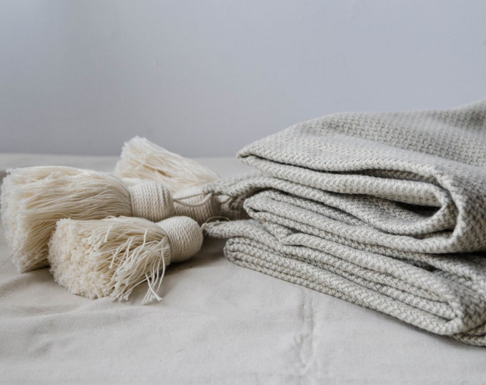 White and gray throw blanket with white tassels.