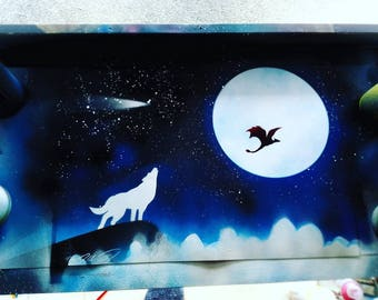 Personalised spray paint art wolf howling at the moon with a dragon.