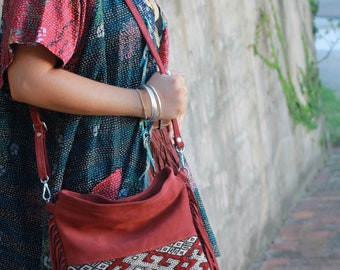 SALE. Suede cross-body bag in rust/maroon with kilim patch on one side. Tassels, zipped closure.
