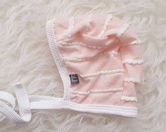 Light pink with white scallop ruffle pilot hat by Little Lapsi. Baby hat with ties.