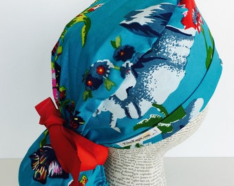 Ponytail Scrub Cap scrub hat featuring a blue material with flowers in shades of blues red green and white with a matching red ribbon