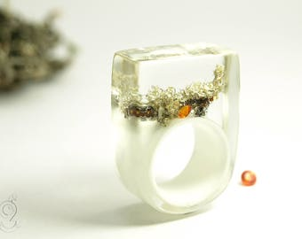 Lichen – Abstract resin ring with an orange zirconia gemstone and a grey lichen on a white ring made of resin