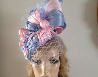 pale blue silk perching hat adorrned with luxurious pale pink and pale blue silks with a scattering of ivory pearls.