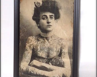 Aged reproduction print of an old time Victorian tattooed lady in frame.