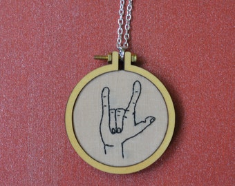 "Embroidered necklace of ""rock hard"" hand gesture"