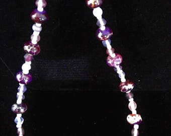 Imperial Pieces. This necklace has purple speckled glass beads as the larger bead and an assortment of purples through out the strand.