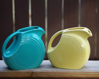 """Vintage Pair of Fiesta Ware 5 1/2"""" Disc Pitchers, Turquoise Blue (1986), Sunflower Yellow. (1986), Made in USA, Marked on Bottom"""