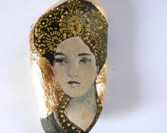 Statuette on a beach stone,woman precious portrait, black and gold