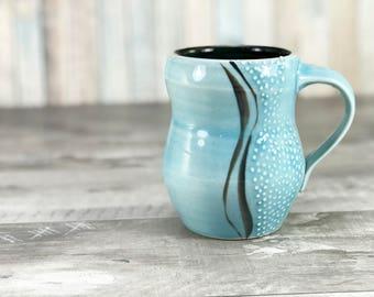 Curvy mug: handmade blue mug with curvy lines and dotted texture. Sky blue glazed mug, black interior. Porcelain mug. Pottery mug. Unique.