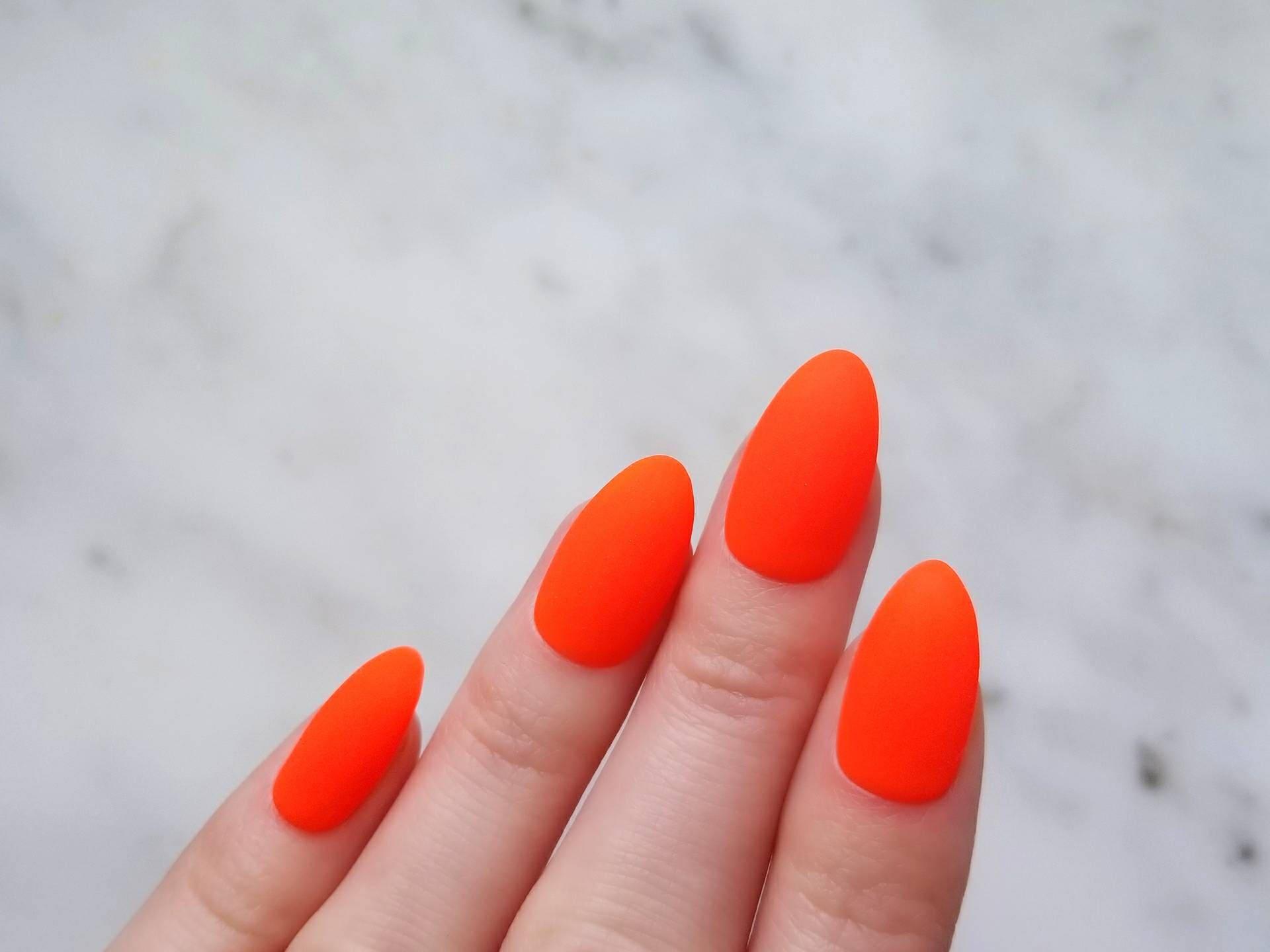 Prensa roja mate neón naranja en las uñas pintado a mano con