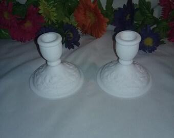 Set of two white milk glass candlestick holders flower design on base.