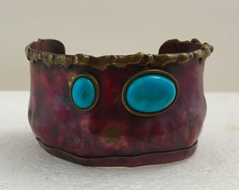 Red copper cuff bracelet with brass accents and turquoise stones.
