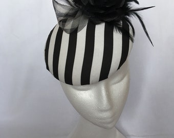 Black and white striped pill box hat with small black flower and checked crin