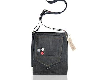 A unique denim shoulder bag, with front pocket and button detail.