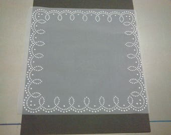 Four squares of white tulle stitched with white designs on the edges
