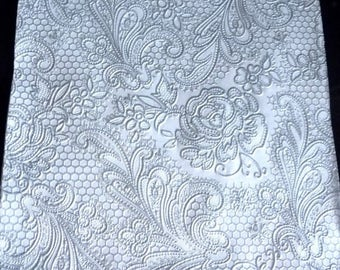 Light grey lace paper on white towel