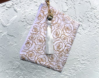 White wristlet/clutch with shimmery gold rose print. Pretty pouch with tassel purse charm. Bridal accessory or evening bag worthy.