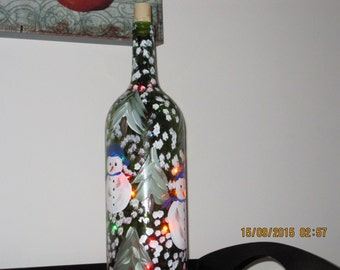 Wine bottle with hand painted Snowman dressed with a blue hat and blue scarf snowflakes falling. Colored lights insde the wine botlle.