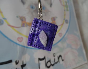 keychains book bright purple with his feather white and pink