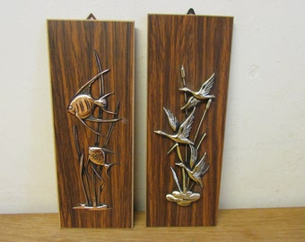 Pair of 1970s copper-tone and wood veneer 3D wall hangings/plaques - fish, & flying geese