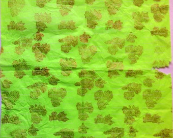 Sheet of lime green tissue paper, woodblock printed by hand in gold